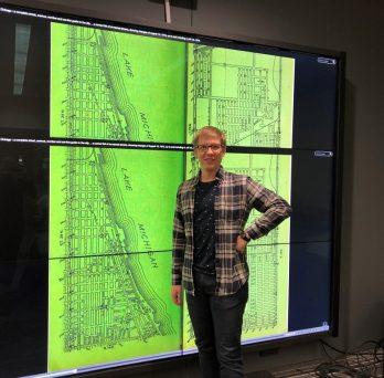 Anton Rozhkov in front of giant map at UChicago Hackathon